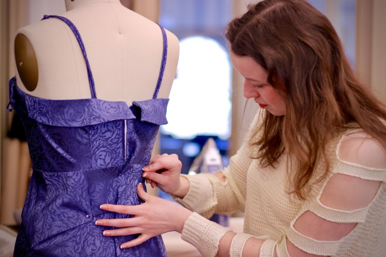 Fashion student pinning a dress.